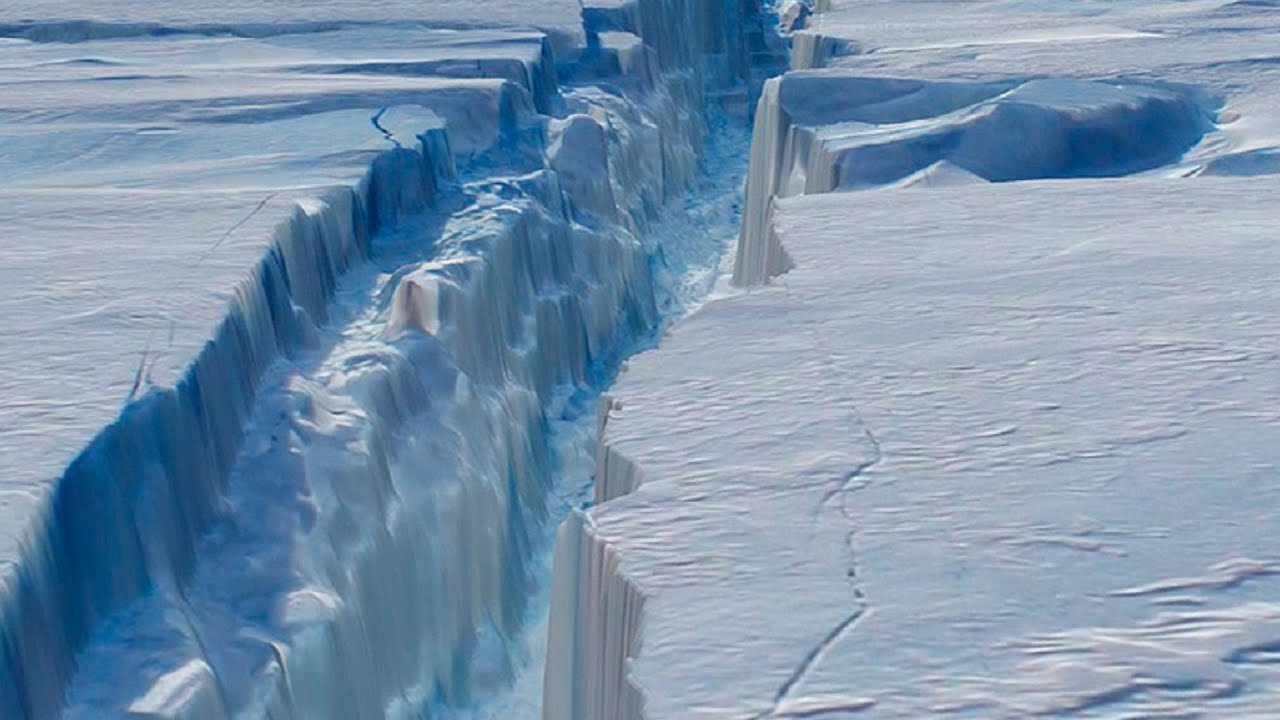 A white and blue photo showing the deep crack in the Antarctic ice shelf. white snow blue and white crack